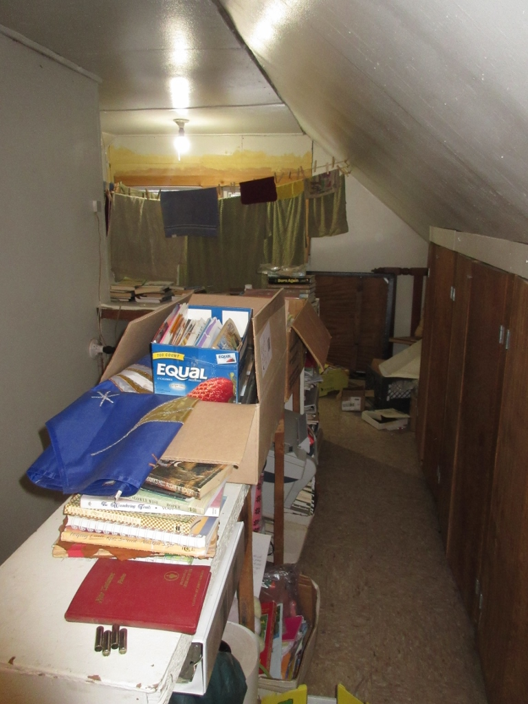 Upstairs storage area/clothesline/future boys' sleeping area. Still sorting through lots of books and materials found in the house.